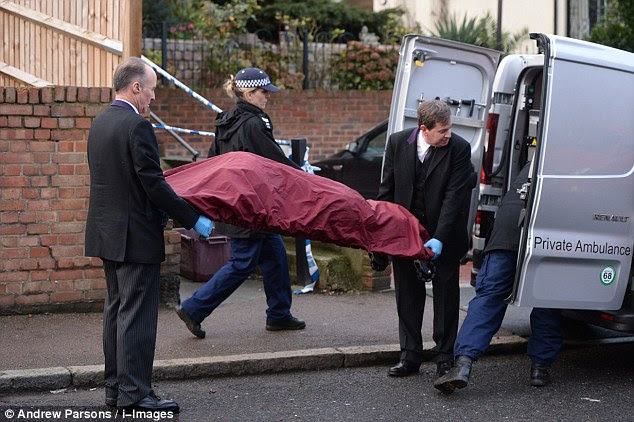 Discovery: The bodies were discovered in the garden of the family home in Erith, south east London. Pictured: Undertakers remove one body from the scene