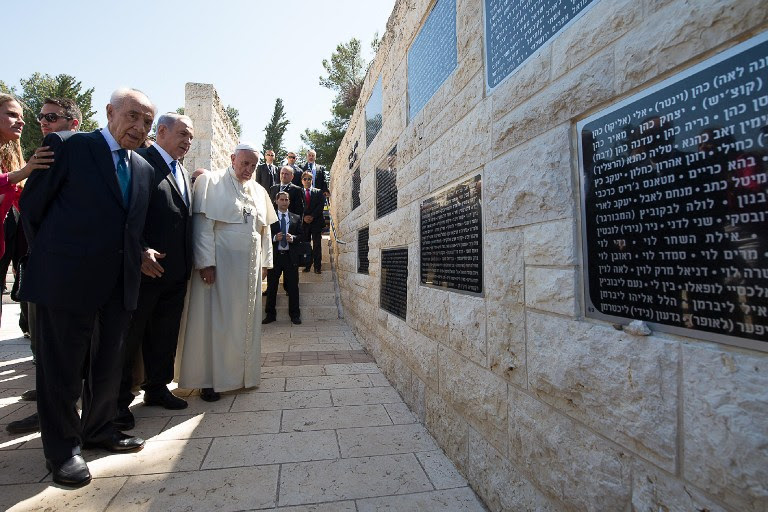 A handout picture released by the Vatican press office shows Pope Francis, looking at a memorial alongside Israeli President Shimon Peres, left, and Israeli Prime Minister Benjamin Netanyahu, second left, at Mount Herzl in Jerusalem on May 26, 2014. (photo credit: AFP/ OSSERVATORE ROMANO)