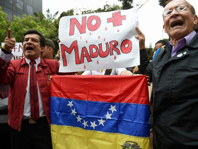 Venezuelans living in Colombia and local people protest against the government of Venezuelan President Nicolas Maduro, in Bogota, Colombia, on April 19, 2017. Clashes broke out Wednesday in Venezuela at massive protests against Maduro, as riot police fired tear gas to push back stone-throwing demonstrators and a young protester was shot dead. Violence erupted when thousands of opposition protesters tried to march on central Caracas, a pro-government bastion where red-clad Maduro supporters were massing for a counter-demonstration. / AFP PHOTO / RAUL ARBOLEDA (Photo credit should read RAUL ARBOLEDA/AFP/Getty Images)