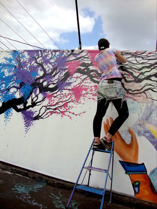 Marina Zumi   Buenos Aires, Argentina Fluir, soltar, paz e consciência são palavras impregnadas no trabalho de Marina Zumi que retrata a expressão da natureza colorida em contraste com o caos cinza da cidade. Sutil, sintética e por vezes pscicodélica, Zumi incorpora técnicas e estilos impulsionados por estudos experimentais e fotografias de suas viagens por aí. Argentina de Lugano, Buenos Aires, formou-se na Escola de Indumentária e teve seus primeiros contatos com a street art aos 18 anos quando começou a aprofundar-se no desenho, expressões e outros meios artísticos.  Marina será mais uma artista a participar da Iª Mostra Artistas Urbanas - Ainda é Preciso, promovida pela Rede Nami a partir do dia 23 de outubro, no CEDIM