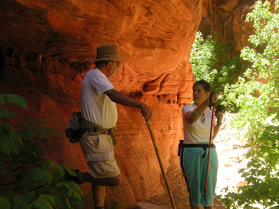 The reflected light in the slot canyon casts a red glow on Larry and Gwen as they examine the rock formations