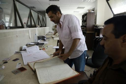Des employés du gouvernement inscrivent des noms de villages et d'habitants dans le registre civil d'Amuda, à l'est de Qamishli en Syrie, le 3 octobre 2016 © DELIL SOULEIMAN AFP