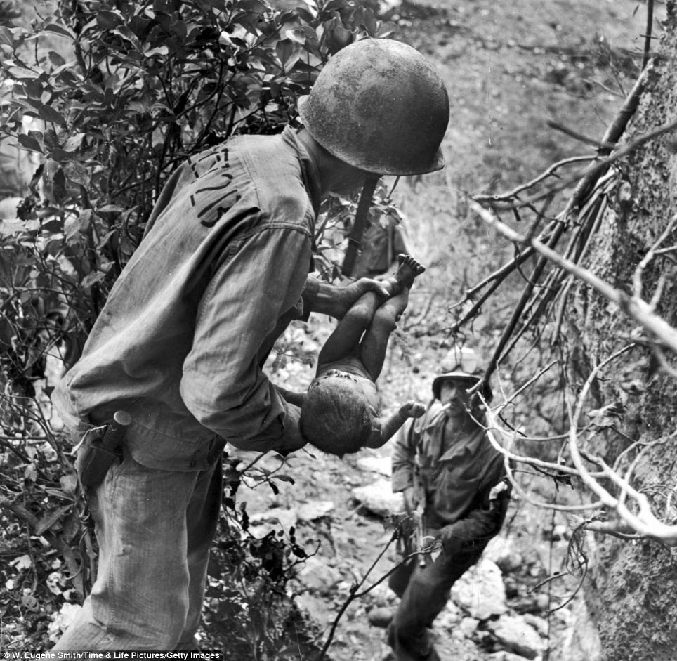 Tenderness: In a July 1944 photograph, an American Marine lifts a nearly dead infant from a cave where native islanders had been hiding during the battle for Saipan, while a second Marine watches from below