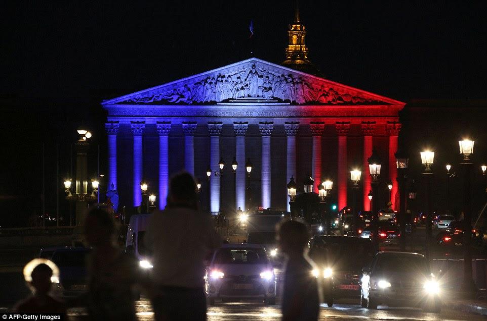 Da Assembleia Nacional Palais Bourbon em Paris iluminado nas cores da bandeira francesa em homenagem às vítimas do ataque na cidade de Normandy de Saint-Etienne-du-Rouvray