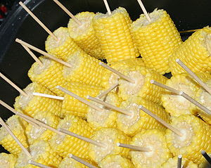 Ears of corn on the cob with sticks, cooked an...