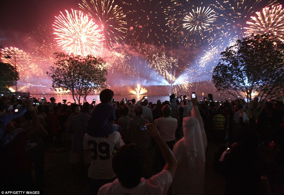 This dramatic image captures the moment some of the thousands of fireworks gave the night sky an orange hue