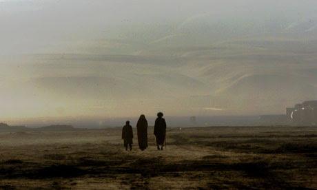 AFGHAN FAMILY WALK THROUGH DESERT NEAR KHOJA BAHAWUDDIN.