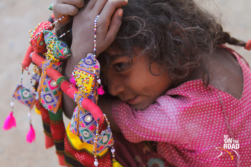 A Nirona kid and her colorful puppet dolls, Kutch, Gujarat, India