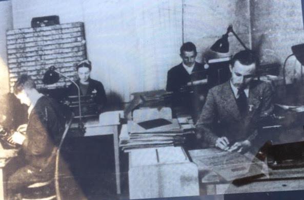 em um escritorio, 3 pessoas trabalhando com papeis, pastas e maquinas de escrever. foto em preto e branco.