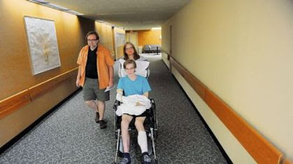 Fran and Bud Yablonsky walk with their son Dan, 23, down a hall Monday at the HealthSouth Harmarville Rehabilitation Hospital in Indiana Township. Dan Yablonsky was seriously injured in a hit-and-run accident in May while riding his bicycle.