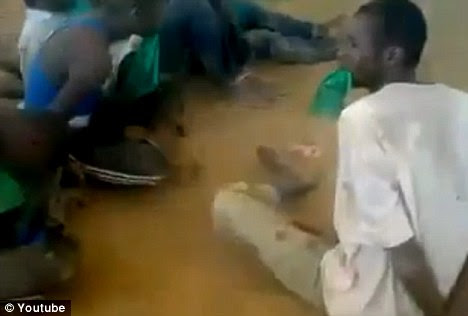 Prisoners: The footage shows a dozen or so men held in what looks like a caged zoo enclosure, with their hands tied behind their backs and the former Libyan flag in their mouths