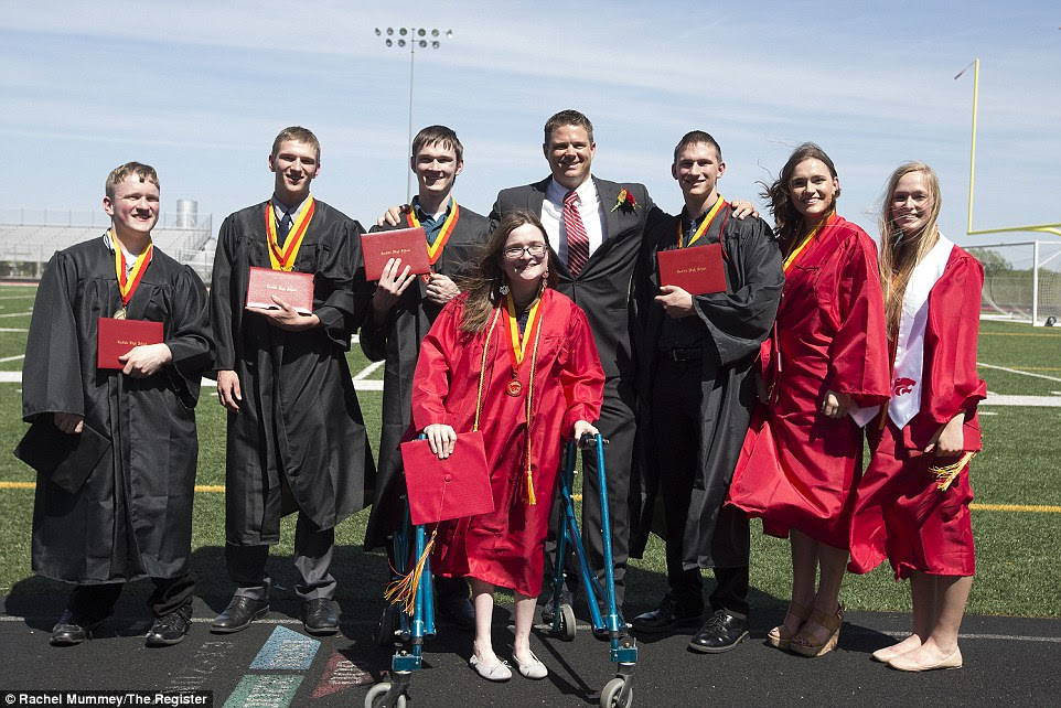 All seven of the McCaugheys - Kenny, Kelsey, Natalie, Brandon, Alexis, Nathan and Joel (pictured with school principal in the suit) graduated from the Carlisle High School in Iowa