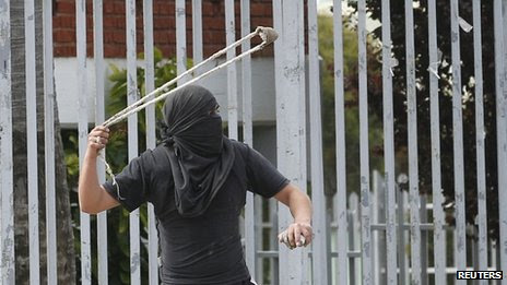 A masked protester throws a stone at a demonstration in Valparaiso on 22 October, 2013