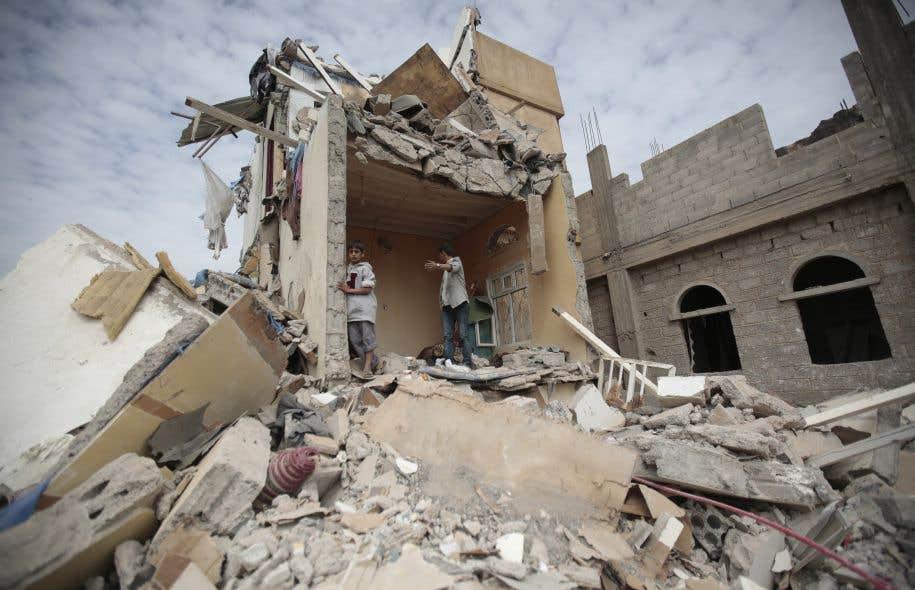 De jeunes garçons yéménites marchent parmi les décombres d'une maison détruite par des raids aériens de la coalition menée par l'Arabie saoudite, à Sanaa, en août dernier.