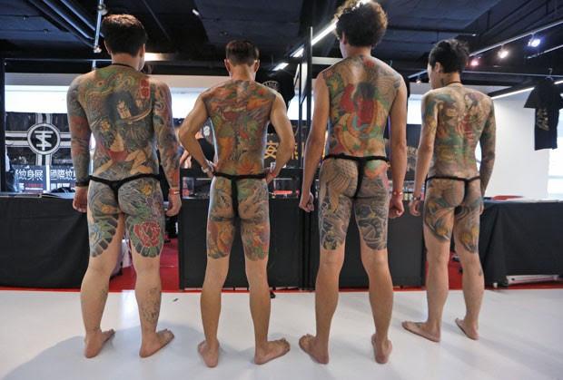 Participantes exibem tatuagens feitas pelo artista taiwanês Diau-An (Foto: Kin Cheung/AP)
