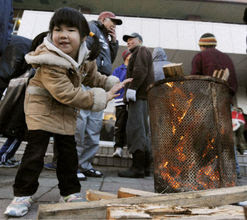 Life at evacuation shelter: A girl warms herself near a fire at the entrance of an evacuation shelter in the quake-hit town of Onagawa in Miyagi Prefecture, northeastern Japan, on March 16, 2011. The area was devastated by a massive earthquake and tsunami on March 11. (Kyodo, used w/o permission)