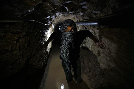 A Palestinian works inside a smuggling tunnel flooded by Egyptian forces, beneath the Egyptian-Gaza border in Rafah, in the southern Gaza Strip in this February 19, 2013 file photo. REUTERS-Ibraheem Abu Mustafa-Files