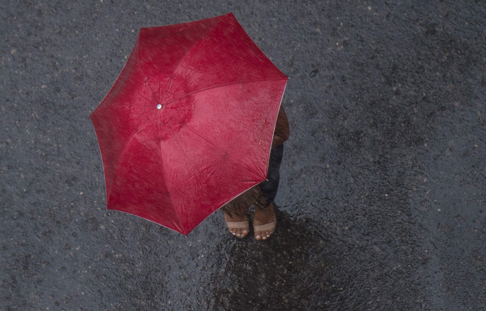 A woman shelters under an umbrella under heavy rain and strong wind in Rio de Janeiro, Brazil