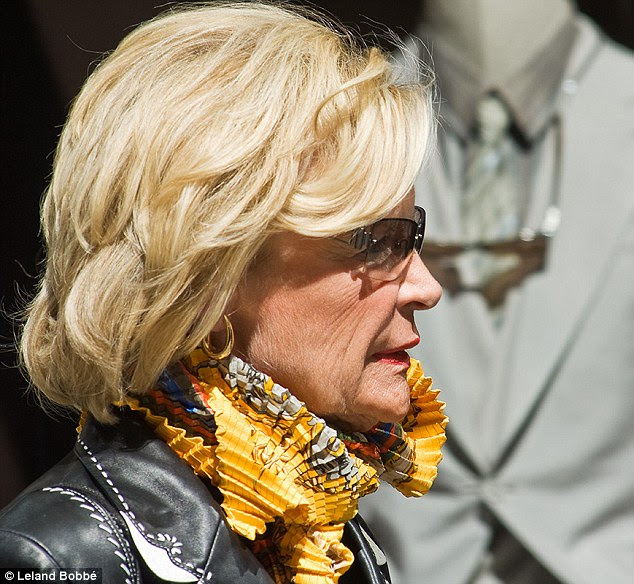 Sunny yellow: This woman takes a leaf out of Chanel designer Karl lagerfeld's fashion book - with a scarf that appears as a high neck, aristocratic collar