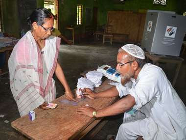 A polling officer puts indelible ink on a voter's finger at a polling booth in Nagaon, Assam. PTI