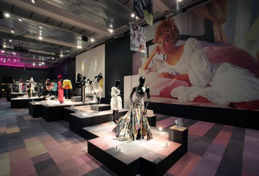 Photo of the exhibition floor, with big picture of Kylie behind mannequins modelling her clothes