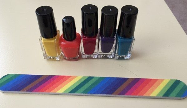 5 mini nail polish bottles in colors that match the PMag logo, and a nail file with rainbow stripes