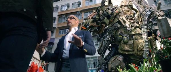 Hound (voiced by John Goodman) tosses his 'cigar' at Joshua's (Stanley Tucci) head in TRANSFORMERS: AGE OF EXTINCTION.