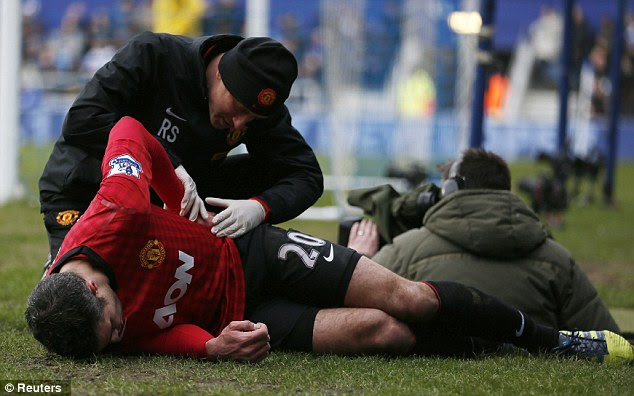 Ouch! Van Persie receives medical treatment after his collision