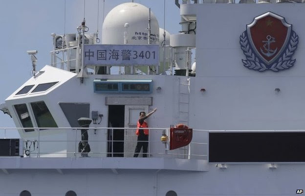 A crewman of the China Coast Guard vessel gestures at the Philippine Government vessel to move away as the latter tries to enter the Second Thomas Disputed Shoals