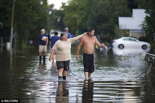 Residents survey flooding in Sorrento on Wednesday.With massive floodwaters receding in Louisiana, officials in the state grappled on Thursday with the next stage of the disaster response - how to help affected residents recover