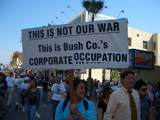 """Photo: sign saying, """"This is not our war, this is Bush Co.'s Corporate Occupation"""""""