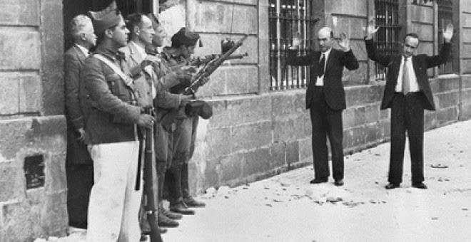 Soldados favorables a Franco encañonan a dos transeúntes, en una calle de Sevilla, al inicio de la Guerra Civil. / EFE
