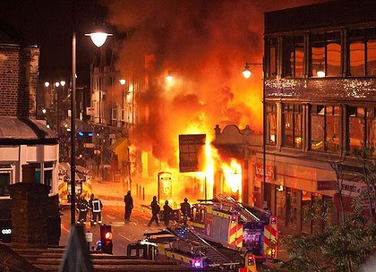 LONDON, ENGLAND - AUGUST 06:  Buildings burn on Tottenham High Road, London after youths protested against the killing of a man by armed police in an attempted arrest, August 6, 2011 in London, England. Twenty-nine-year-old father-of-four Mark Duggan died August 4 after being shot by police in Tottenham, north London. (Photo by Matthew Lloyd/Getty Images) *** BESTPIX ***