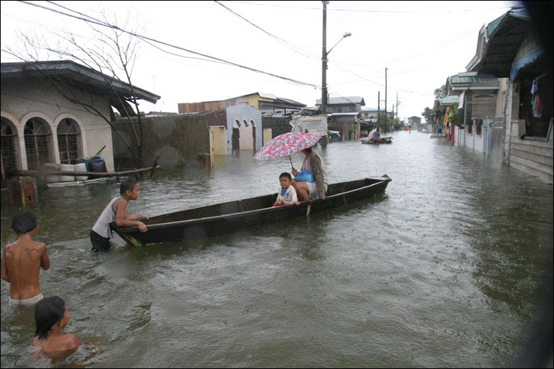 Residents use a boat for transport on the flooded streets in Dampalit north of Manila