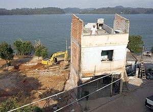 Pedreiro Jesuino Ferreira observa máquina derrubar casas ao lado da sua, que também será derrubada, para obras em SP