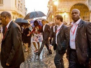 El presidente estadounidense, Barack Obama, camina bajo la lluvia con la primera dama Michelle Obama, que sostiene el brazo de su madre Marian Robinson, durante un recorrido a pie por La Habana Vieja, en Cuba.
