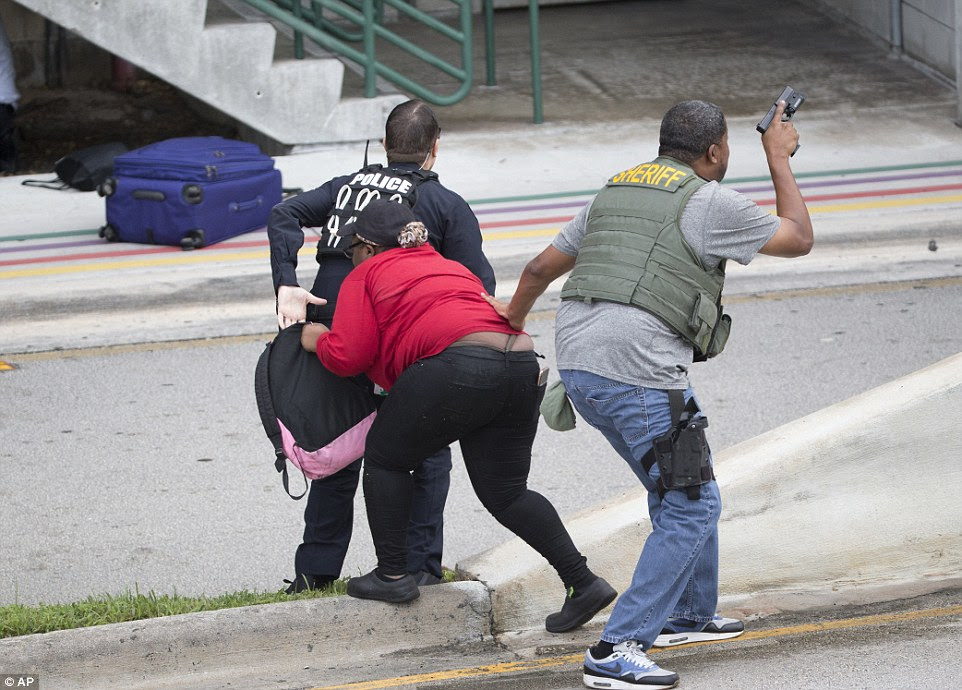 Police evacuate a civilian from an area at Fort Lauderdale Airport about 3pm on Friday after the shooting