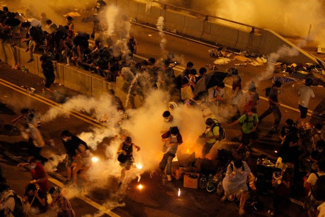 <p>Riot police fire teargas to disperse protesters after thousands demonstrated in the main street to the financial Central district.</p>