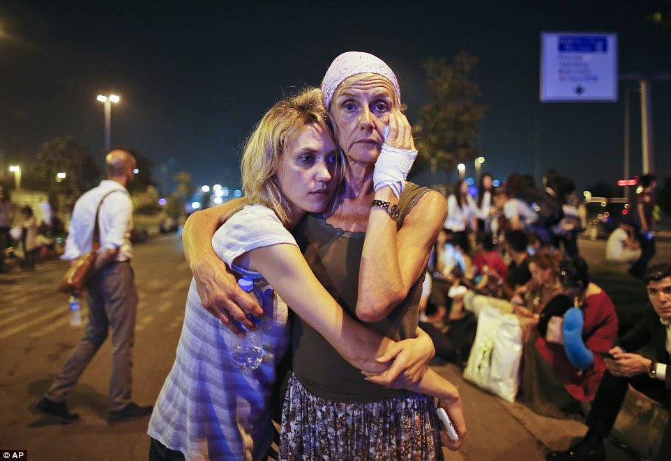 passageiros desesperados abraçar como eles se reúnem em estado de choque fora do terminal após o aeroporto foi evacuado e todos os vôos foram cancelados