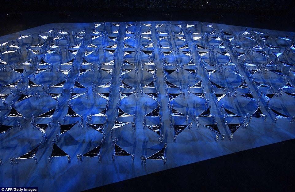 Performers, vestida em prata e agitando bandeiras de prata, criado padrões geométricos no chão no início da cerimônia de abertura