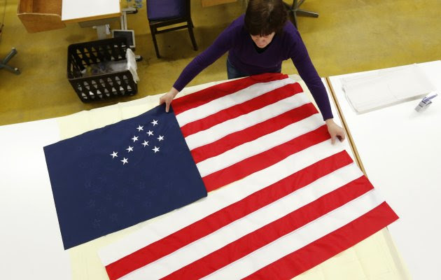 A worker adjusts pieces of a U.S. national flag at the Waelkens flag company in Oostrozebeke February 4, 2013. When U.S. President Barack Obama was sworn in for his second term on January 21, it's a decent bet that one of the flags fluttering behind him on the U.S. Capitol was made in Belgium. The Waelkens flag company, based in the small town of Oostrozebeke in Flanders, supplies around 2,000 flags a year to the United States, with clients including the Pentagon and other U.S. government departments as well as the United Nations. Picture taken February 4, 2013.  REUTERS/Francois Lenoir (BELGIUM - Tags: POLITICS BUSINESS)