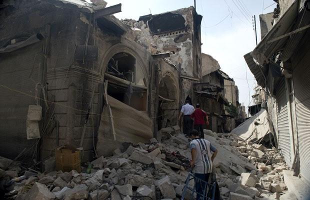Sírios inspecionam danos em Aleppo depois que área foi bombardeada pelo exército sírio (Foto: Miguel Medina/AFP)