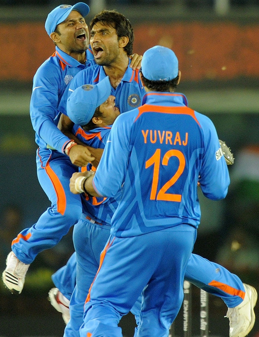 Yuvraj Singh, Virender Sehwag and Suresh Raina rush to celebrate the fall of a wicket with Munaf Patel