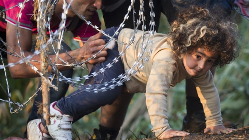 A refugee girl moves under barbed wire as she crosses from Serbia to Hungary [AP]