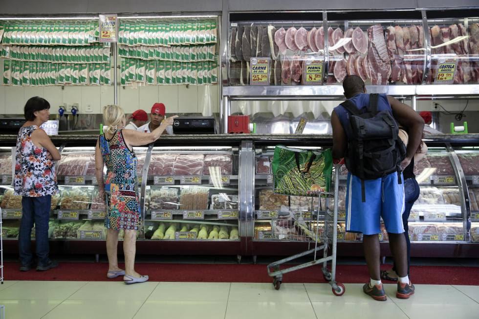 Clientes compram carne num agouçe em São Paulo.
