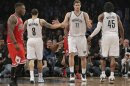 Brooklyn Nets' Williams, Lopez and Wallace tap hands as Chicago Bulls' Robinson walks off the court in the fourth quarter of their NBA basketball playoff game in New York