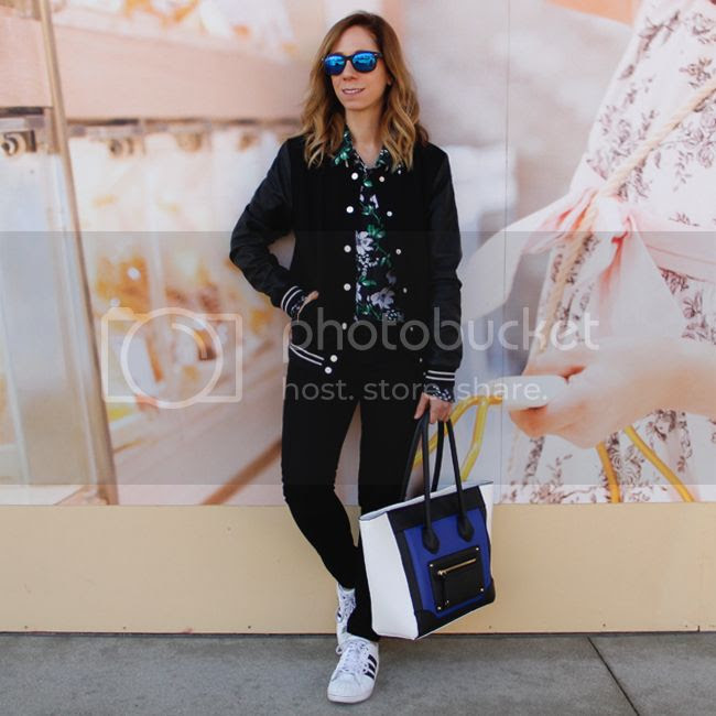 Fashion blogger The Key To Chic wears an Equipment floral silk blouse, J Brand skinny jeans in black, Mossimo colorblock handbag, and Adidas superstar 2 sneakers.