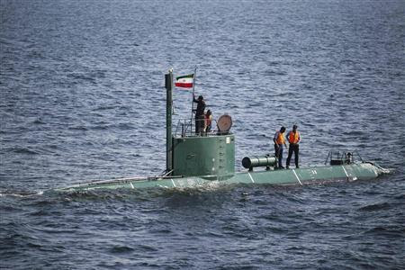 Military personnel place a flag on a submarine during the Velayat-90 war games by the Iranian navy in the Strait of Hormuz in southern Iran December 27, 2011. REUTERS-IIPA-Ali Mohammadi