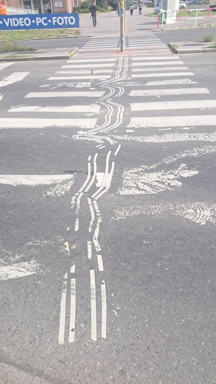 Guiding Tracks For Blind People On This Crosswalk Got Distorted Due To Cars Acceleration Forces Combined With Viscose Asphalt Over Time