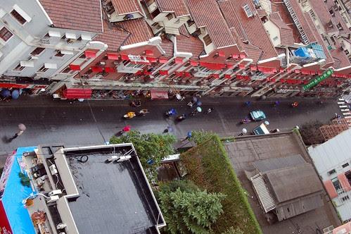 Im Regen von oben, eine Verkaufsfront von Geschäftshäusern in einer Strasse im Huangpo Viertel in Shanghai. Mehrere Radfahrer in bunter Regenkleidung